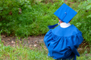 A little boy dressed in a blue graduation cap and gown.